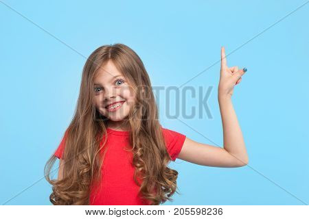 Little girl looking at camera with amazement pointing up on blue background.