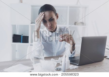 Sick woman sitting at her workplace in the office. She has a pack of headache pills in her hands. She holds her hand to the head