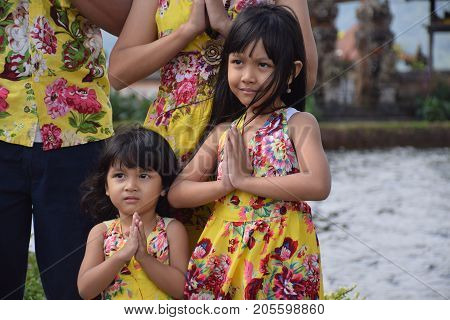 BALI, INDONESIA, AUGUST 22, 2017 - Two beautiful balinese babies posing for a picture inside Ulun Danu hindu temple on the water