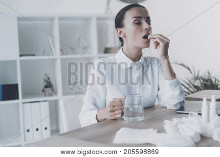 Sick woman sitting at her workplace in the office. She holds a tablet that she is going to swallow. She already held it to her mouth