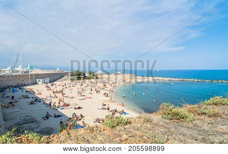 Antibes France - July 01 2016: people sunbathing on Plage de la Gravette in Antibes. It is a popular local beach a long stretch of fine white sand at the end of the port.