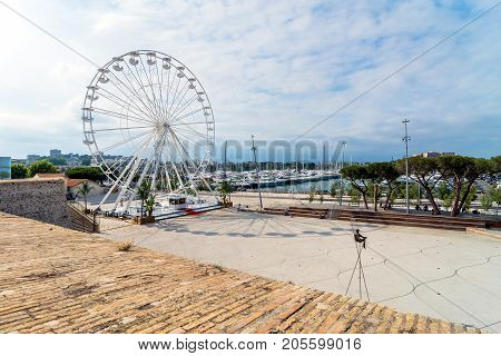 Antibes, France - July 01, 2016: Modern art sculptures and grande roue on the Pre-des-Pecheurs esplanade in the old town. The area was renovated in 2014 and is popular for events.