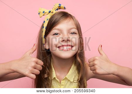 Portrait of little model wearing headband and smiling at camera showing thumbs up on pink.