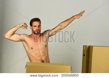 Sexuality And Moving In Concept: Naked Superhero Among Boxes