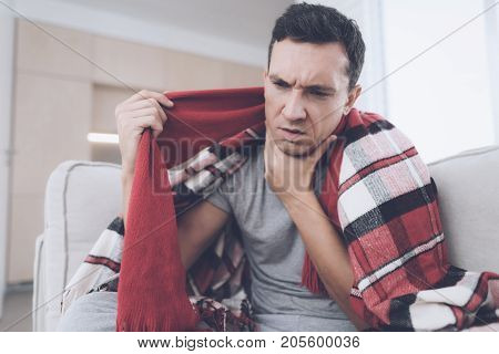 A man with a cold sits on the couch, hiding behind a red rug. He's holding his throat because it hurts badly.