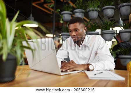 Serious african man in headphones, listening music, typing, working at laptop in stylish cafe. Handsome freelancer looking at screen, writing message. Student learning. Coffee break. Loft interior.