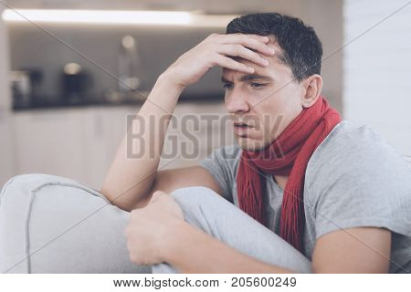 A man with a cold sits on the couch, hiding behind a red rug. He has a bad headache and a high fever