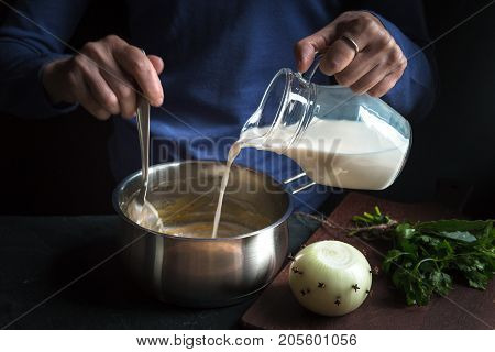 Milk from the jug is poured into a base sauce for making bechamel horizontal