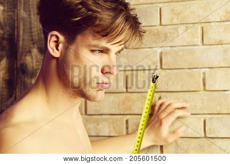 Man With Naked Body Holds Yellow Self Retracting Tape Measure