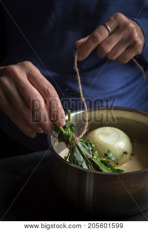 Preparation of bechamel sauce, onion and bouquet garnish in hands vertical