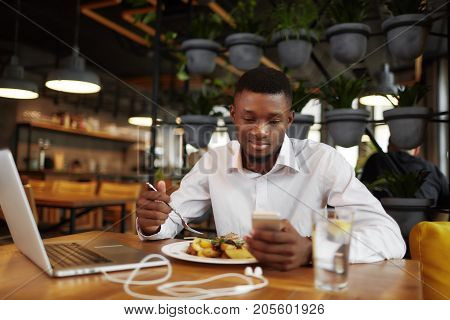 African business man having dinner eating at restaurant working with laptop, reading message in smart phone. Handsome male student at coffee break using call phone. Freelancer job.