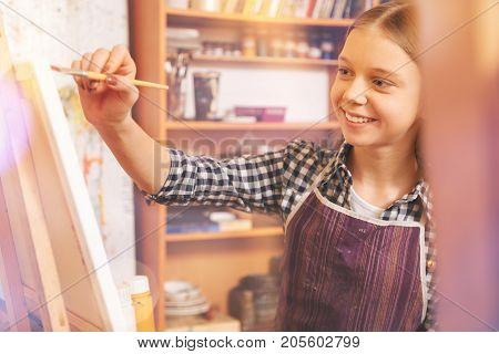 Favorite leisure time activity. Selective focus on an adorable blonde little lady wearing an apron and sitting at an easel while working on a new painting in an art workshop.