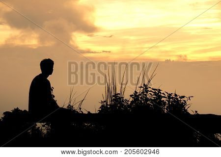 Silhouette Man sitting watch the evening sky at sunset