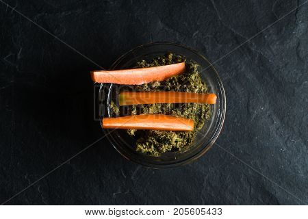 Pesto of carrot tops and carrots on a gray background horizontal