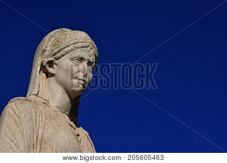 Vestal Virgin priestess ancient statue from the Temple of Vesta ruins in Roman Forum (with blue sky and copy space)