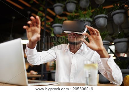 African man wearing in glasses of virtual reality on head, pointing in air by hands gesturing and touching. Young male in white shirt watching video, playing game. Imitation of reality with technology.