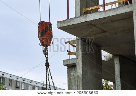 Construction crane carries materials on construction site with a part of dwelling house on the background.