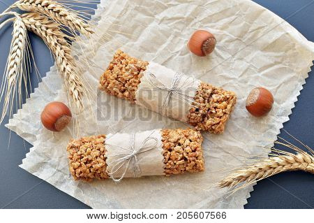 two muesli bars with filbert nuts and wheat ears on backing parchment background