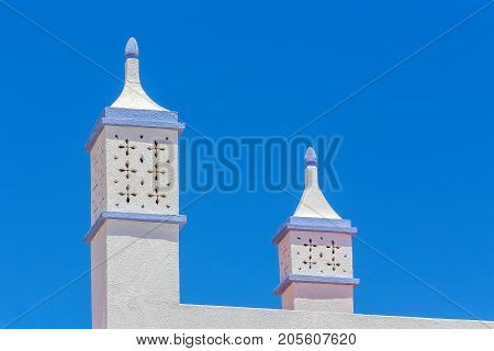 Graceful white chimneys on building with blue sky