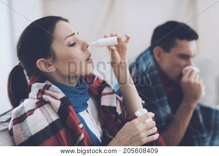 The couple is sitting on the couch wrapped in blankets. Man and woman are sick. A man blows his nose, a woman sprinkles herself with a nose spray