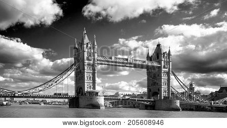 Tower Bridge spanning the River Thames with a dramatic cloudy sky in black & white