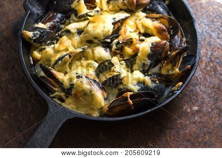 Frying pan with mussels under cheese sauce on a brown background side view horizontal