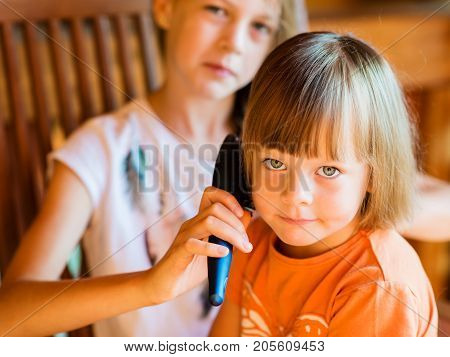 Charming little girl is looking at camera and smiling while her beautiful older sister is combing her hair