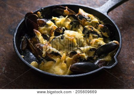 Cooked mussels in a cast-iron frying pan with cheese sauce horizontal