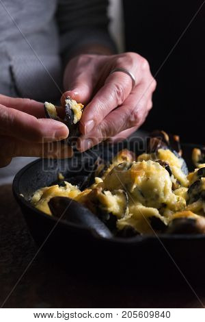 Female hands over a frying pan with mussels under cheese sauce vertical