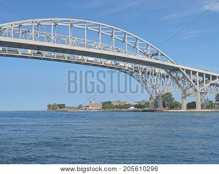 The two spans of the international Blue Water Bridge join Sarnia, Ontario, Canada (seen in this image) and Port Huron, Michigan, United States of America. Here the waters of Lake Huron, one of the Great Lakes, flow into the St. Clair River on the way to L