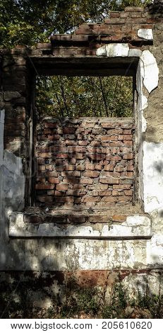 Fragment of old destroyed house with a window. Old architecture.Old window. Historic arhitecture. Destroyed house.
