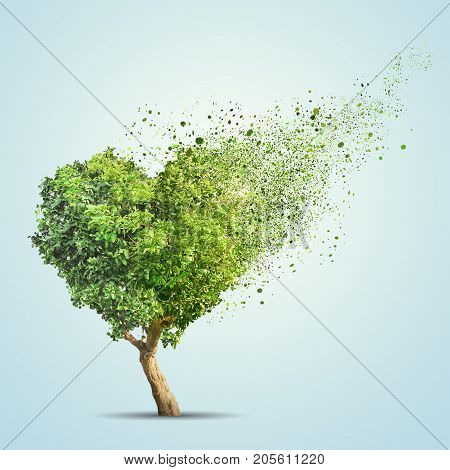3d illustration of green tree shaped in heart disintegrate over blue background