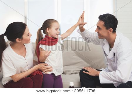 The little girl caught a cold. Her mother called the doctor at home. Girl, mother and doctor smiling. The girl gives the doctor high five