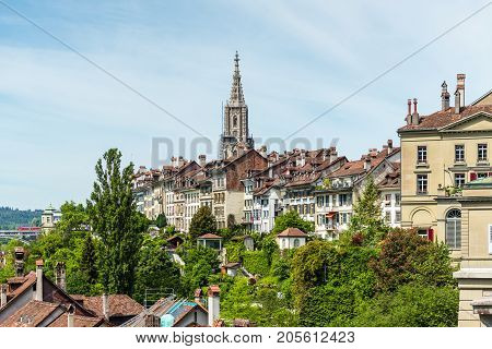 Picturesque panorama of the old town. The tall steeple of the Bern Minster that is rising high above the city buildings of Bern Switzerland