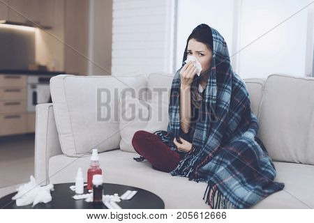 A cold woman sits on a light couch wrapped in a blue checkered whip. She blows her nose into a napkin with a plaid over his head