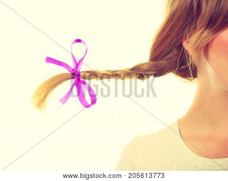 Hairstyles haircare concept. Closeup of braided blonde hair with bow. Studio shot on light background