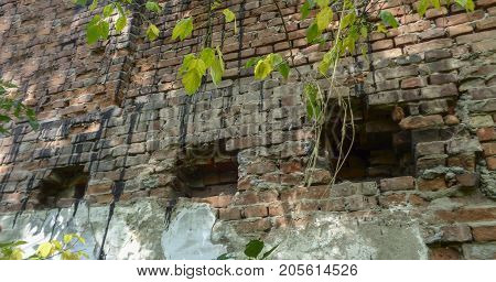 Fragment of the wall of a very old building. Old architecture. Holes in the wall