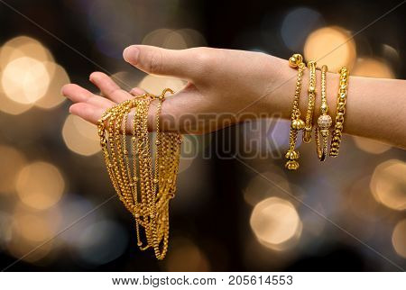 woman hand hold gold bracelet and necklace jewelry