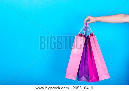 Female Hand Holding Colorful Shopping Bags Isolated On Blue (cyan) Background, Free Space, Close Up.