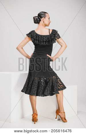 young woman in black dress in studio, beautiful dancer turning backwards