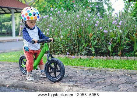 Cute little Asian 1 years / 18 months old baby boy child wearing safety helmet learning to ride his first balance bike in spring time kid playing & cycling in garden Child first experience concept
