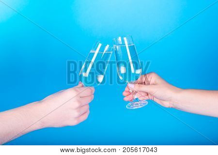 Close-up Of Two Glasses And Two Hands, Free Space. Man And Woman Clanging Wine Glasses With Champagn