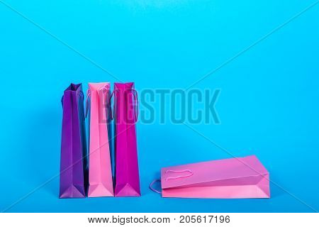 Colorful Paper Shopping Bags Isolated On Blue (cyan) Background, Free Space. Bright Gift Bags For Ch