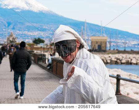Pulcinella and people, traditional Neapolitan mask gestures with snowy Vesuvius in the background in the Gulf of Naples. Actor recites the part of Pulcinella in the street, among the people who pass, on the promenade of Naples