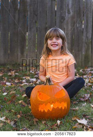 a little girl with her pumpkin at halloween.