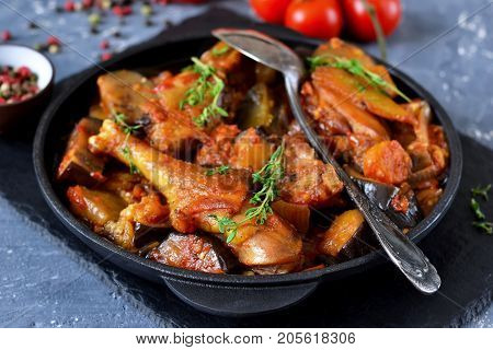 Chicken stewed with vegetables and tomato on a stone board in a frying pan.