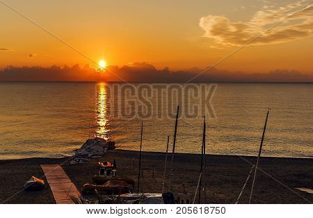 calm sea at dawn with a rocky beach with boats