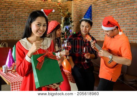 Young Asian smile girl with Santa hat get surprise gift in bag from boyfriend while others cerebrate by drinking red champagne and playing ukulele. Christmas party concept with copy space for text.