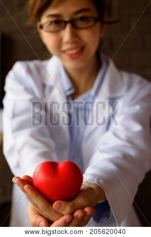 Female Doctor With Red Heart On Hand