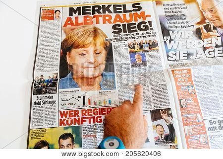 PARIS FRANCE - SEP 25 2017: Die Bild german newspaper man reading with portrait of Angela Merkel after election in Germany for the Chancellor of Germany the head of the federal government